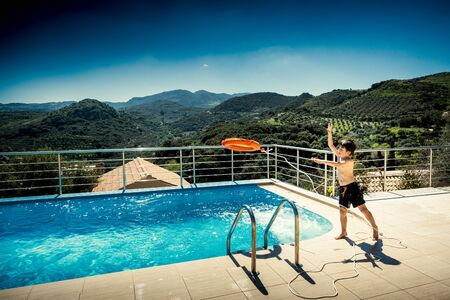 Playful boy throwing buoy in swimming pool with mountains in background Reklamní fotografie