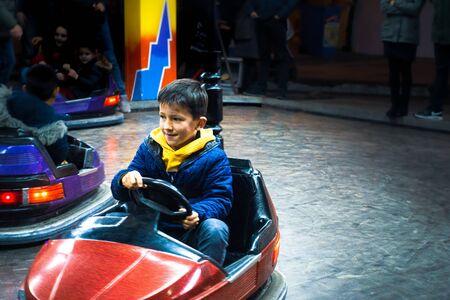 Boy having fun riding bumper car at amusement park