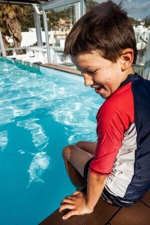 Boy sitting by swimming pool, Crete, Greece 版權商用圖片
