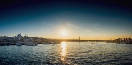 View of ship at harbor with bridge in the background during sunset, Istanbul