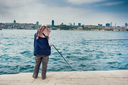 Man fishing on the sea with cityscape in the background, Istanbul