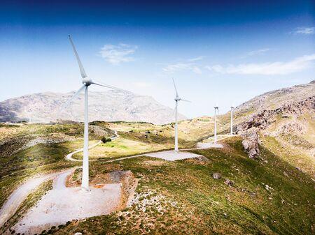 Row of wind turbine on cliff against sky