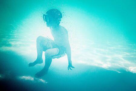 Boy swimming underwater in swimming pool, Crete, Greece