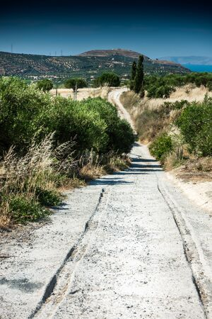 Trace of tire track over winding roads surrounded by field of Crete Island, Greece Banque d'images