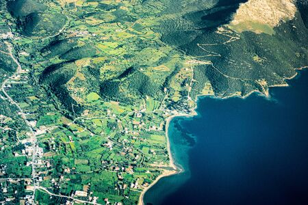 Aerial view of island with coastal agricultural field and mountain, Crete, Greece