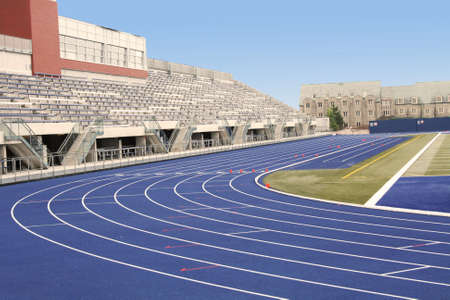 Picture of a track and field stadium with empty stands Фото со стока