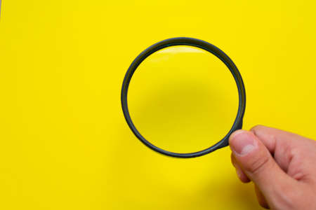 Hand holding a black magnifying glass isolated over a bright yellow background, on the right bottom corner
