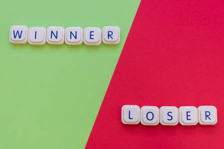 Winner and loser words made with board game letters, with the winner on the green side and the loser on the red side of the image. Competitors and rivalry concepts