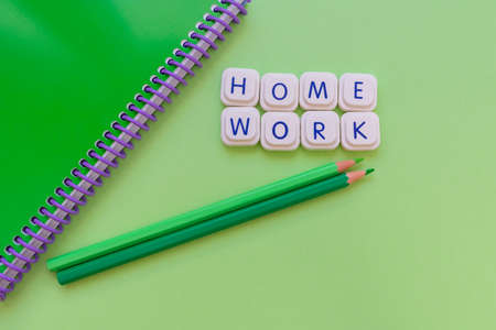 Home work message made with board game letters, with a green notebook and two green pencils, over a green background. Studies and work concept