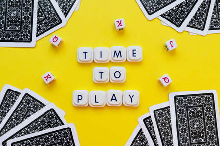 Time to play message made with board game letters, over a bright yellow background, surrounded by dice and playing cards on the corners of the image