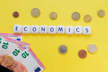 Economics word made with board game letters, with euro coins and bills, over a bright yellow background. Illustration of economic and money
