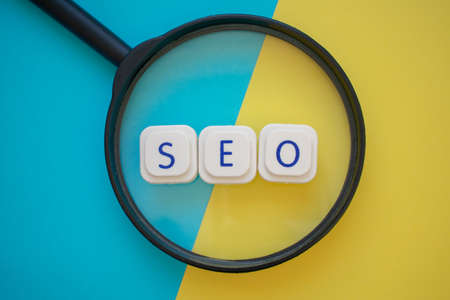 "The word ""SEO"" is over a magnifying glass, over a yellow and blue background. Web search and positioning concepts. Search engine optimization concept"