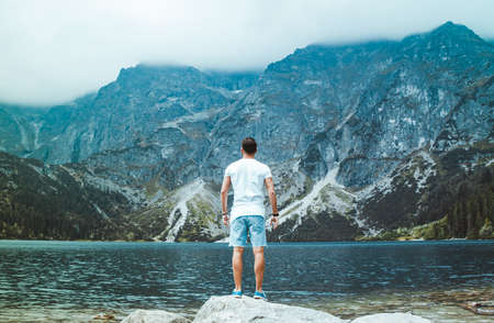 A picture of a young, explorer-type man in the Morskie Oko lake, Tatra Mountains, Poland. Stock Photo