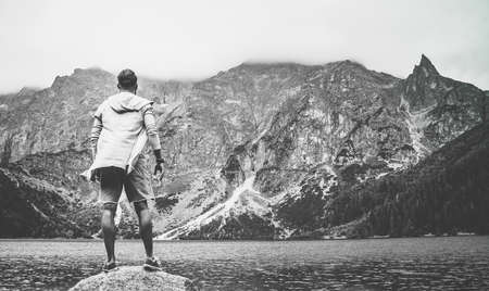 A black and white picture of a young, explorer-type man in the Morskie Oko lake, Tatra Mountains, Poland.