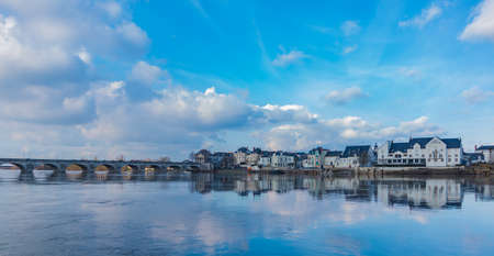 A picture of the Offard Island, i.e. the other side of Saumur, against a blue sky and its reflection on the river. Editorial