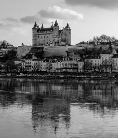A black and white picture of the Château de Saumur taken from the other side of the river. Stock Photo