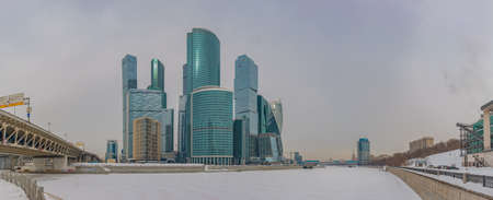 A panorama of the Moscow City buildings and the adjacent river.