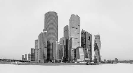A black and white panorama of the Moscow City buildings and the adjacent river.