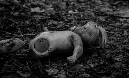 A black and white picture of a broken doll outside an abandoned kindertgarten. Stock Photo
