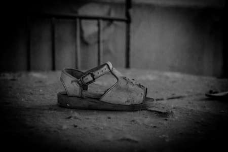 A black and white picture of a single baby sandal inside an abandoned kindergarten. Stock Photo