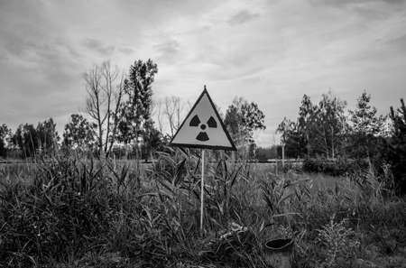 A black and white picture of a radiation sign between some vegetation near Chernobyl.