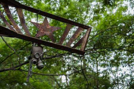 A picture of a gas mask hanging off a soviet symbol in Pripyat.