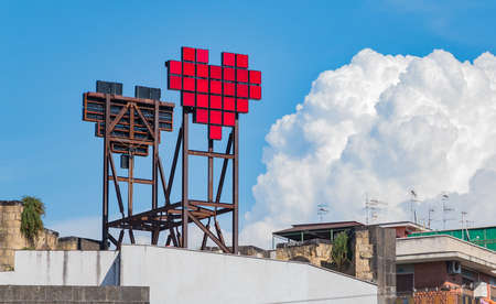 A picture of a pixelated heart at the top of a building, in Naples.