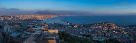 A panorama of Naples featuring Mount Vesuvius in the distance.