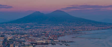 A picture of Mount Vesuvius and the port area of Naples, at sunset.