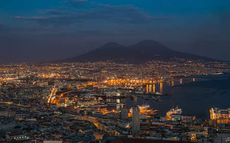 A picture of the port area of Naples, as well as Mount Vesuvius in the distance, in the early evening.