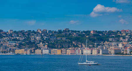 A picture of a sailing boat with the Chiaia district in the back (Naples).