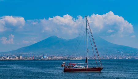 A picture of a sailing boat with Mount Vesuvius in the back (Naples).