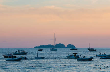A picture of a group of resting boats across the shore from Positano, at sunset. Editorial