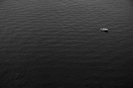 A black and white picture of a small fishing boat alone in the vastness of the sea. Stock Photo