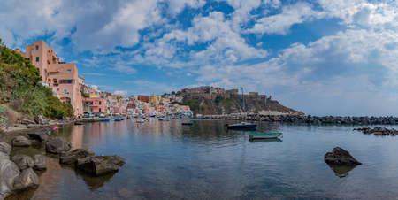 A panorama picture of the Marina della Corricella, the colorful promenade in Procida, Naples.