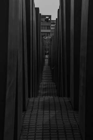 A black and white picture of a corridor inside the Holocaust Memorial, in Berlin.