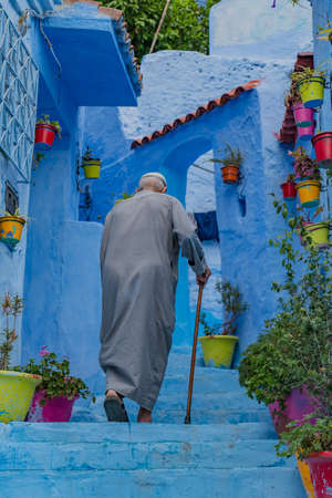 A picture of an elderly man going up some stairs in Chefchaouen. 免版税图像