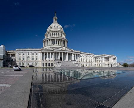 Une photo panoramique du Capitole des États-Unis se reflétant sur une surface voisine.