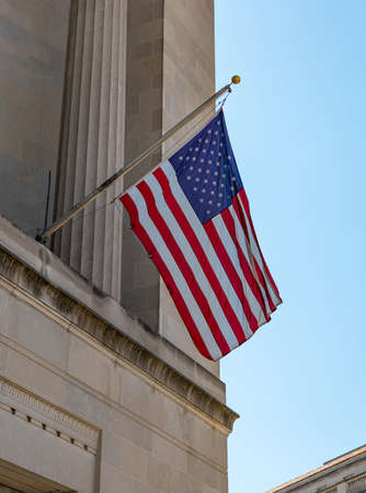 A picture of an American flag hanging off a building, in Washington.