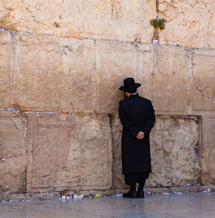 A picture of a Jewish man praying at the Wailing Wall.