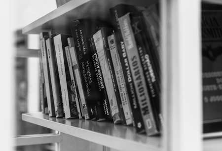 A black and white picture of a group of books sitting on a shelf inside a phone booth. Standard-Bild
