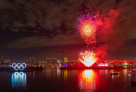 A picture of the fireworks commemorating the opening of the Olympic Rings in the Tokyo Bay, featuring the Rainbow Bridge, at night (Tokyo).