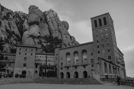 A black and white picture of the Santa Maria de Montserrat Abbey's facade and square.