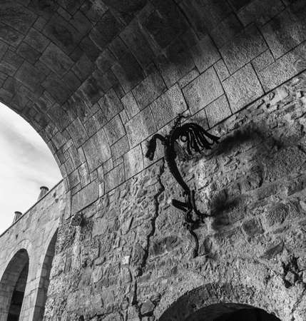 A black and white picture of a metal decorative dragon attached to the entrance tunnel of the Ljubljana Castle. 免版税图像