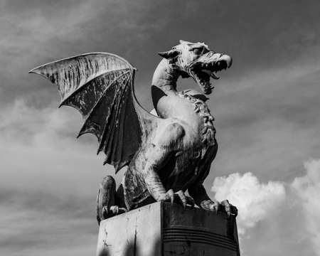 A black and white picture of one of the dragons that decorate the Dragon Bridge.