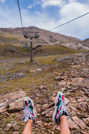 A picture of someone's shoes while riding the ski lifts of Sierra Nevada.