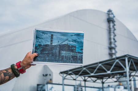 A picture of someone showing a picture of the old sarcophagus that protected the fourth reactor of the Chernobyl nuclear power plant in front of the new dome.