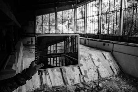 A black and white picture of someone showing a picture of the swimming pool of Pripyat against the current abandoned scenario.
