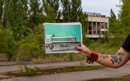 A picture of someone showing a picture of the old Pripyat community center against the current abandoned scenario. 新聞圖片