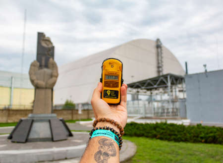 A picture of someone holding a giger counter in front of the Chernobyl nuclear power plant. 版權商用圖片 - 159073660